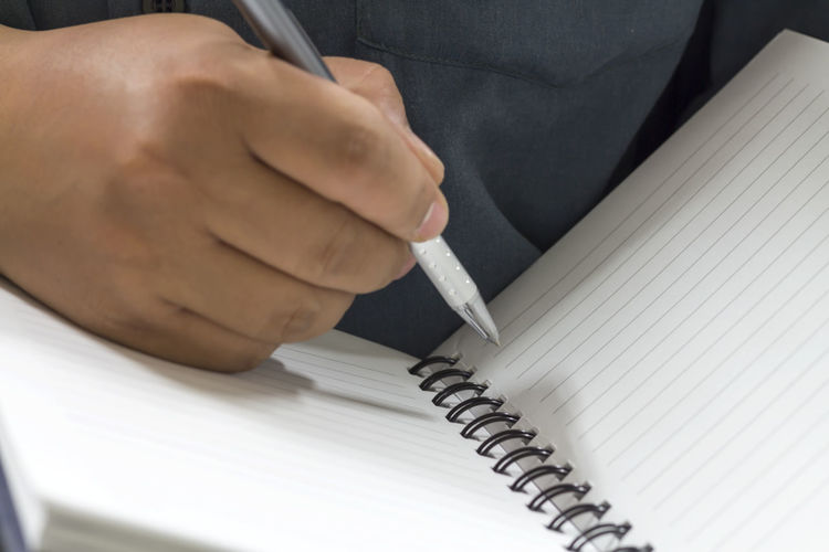 Midsection of man writing on notebook