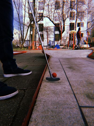 Low section of person with ball on street in city