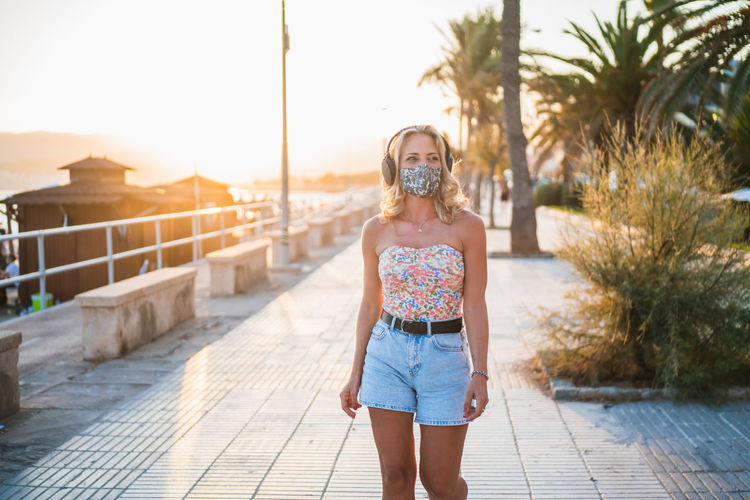 Young woman wearing flu mask walking on street against sky