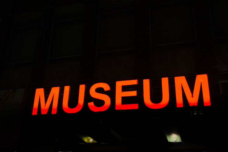 Red illuminated sign saying museum at night Text Night Illuminated Western Script Communication Neon Sign Capital Letter Red No People Glowing Architecture Lighting Equipment Low Angle View Building Exterior Dark Close-up Information Outdoors City Black Background Nightlife Museum