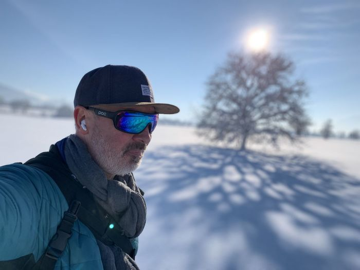 Man wearing sunglasses on snow field against sky