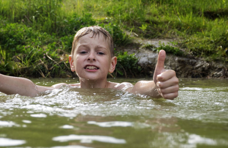 Shirtless boy swimming in river at forest
