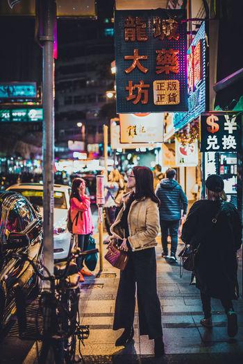 Rear view of people walking on illuminated street