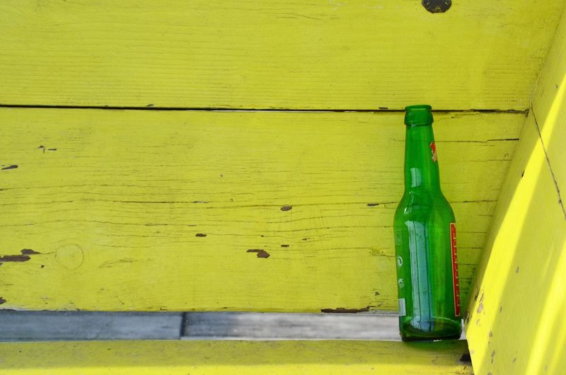 Close-up of green bottles on wooden table