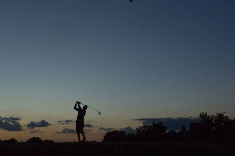 Silhouette man playing golf course on field against sky during sunset