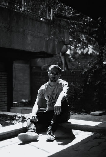 Analogue Photography Film Ilford Film Analog Photography Architecture Blackandwhite Blackandwhite Photography Building Exterior Casual Clothing City Day Film Photography Front View Full Length Leisure Activity Lifestyles Looking At Camera Men Nature One Person Outdoors Real People Sitting Sunlight Young Adult Young Men