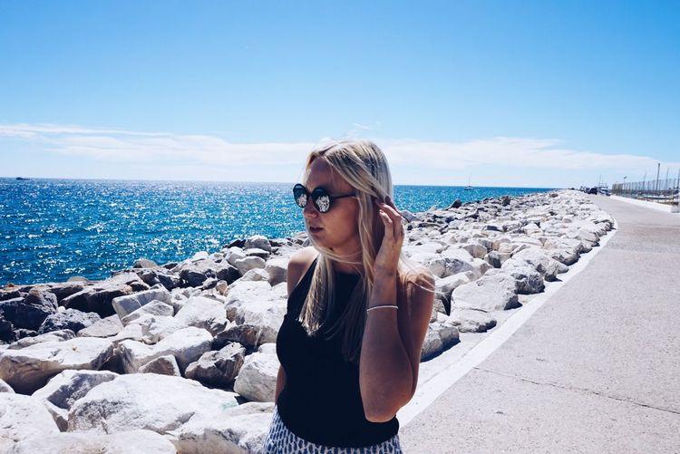 Beautiful Woman Standing On Footpath By Groyne Against Sea