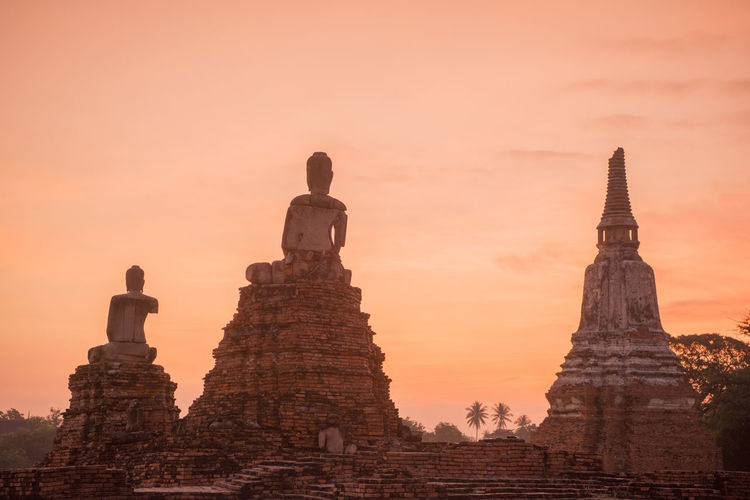 Low Angle View Of Buddha Statues And Temple Against Sky During Sunset