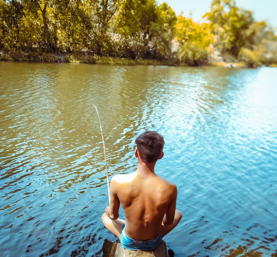 The alone boy is fishing on the river