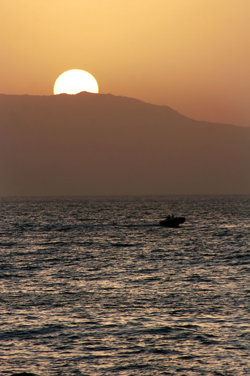 sunset, beauty in nature, sea, scenics, nature, water, waterfront, orange color, tranquil scene, silhouette, tranquility, sun, outdoors, mountain, sky, no people, idyllic, horizon over water, clear sky, nautical vessel, day
