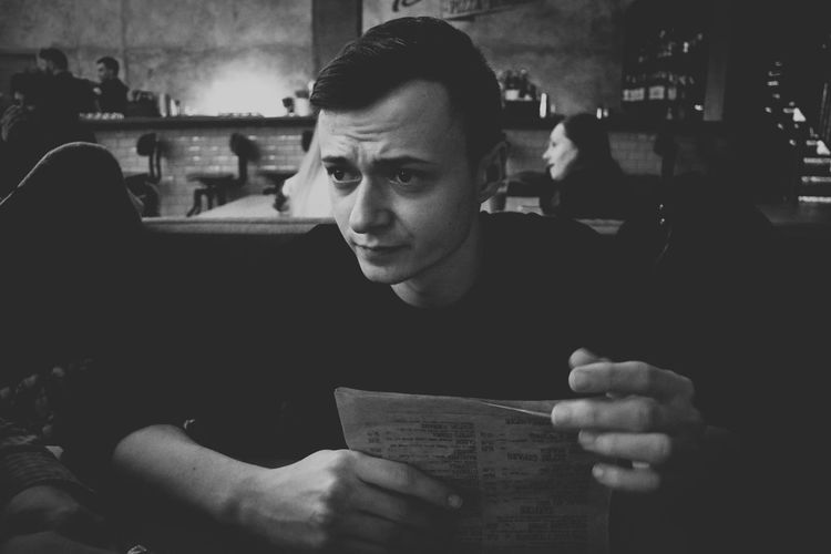 Young man with menu looking away while sitting in cafe