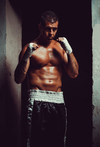 Portrait of shirtless male athlete wearing hand wrap while standing against wall