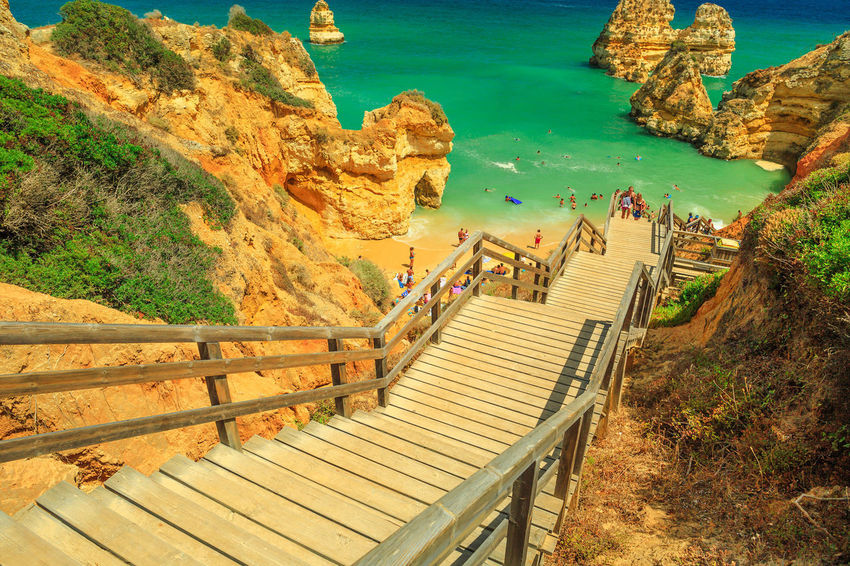 Panoramic wooden walkway footbridge to scenic Praia do Camilo in Lagos coast, Algarve, Portugal. Perspective view downward of the long stairs to turquoise waters of Algarve. Summer holidays in Europe. Lagos Portugal Algarve Portugal Algarve Coastline Algarve Beach Algarve Cliffs And Beach Beach Sea Town Seascape Boat Portrait Pier Aerial View Cliff Jetty Boats Camilo Beach Praia Dona Ana Praia Railing Group Of People Water Staircase Nature Architecture High Angle View Real People Day Beauty In Nature Scenics - Nature Mountain Men The Way Forward Direction Leisure Activity Land Rock Steps And Staircases Outdoors Footbridge