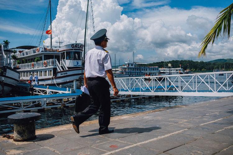 Full length of man standing at harbor against sky