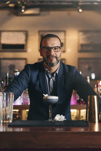 Portrait Of Smiling Bartender Standing At Counter In Bar