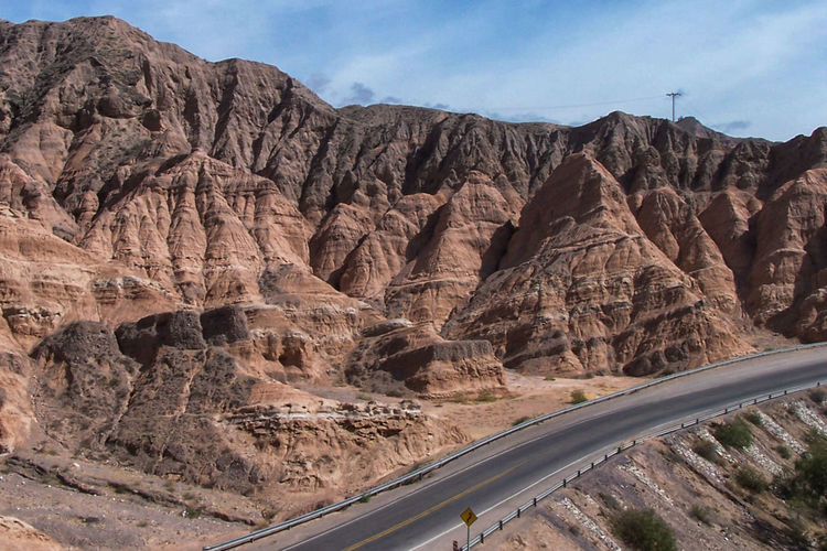 High angle view of empty road between barren mountains