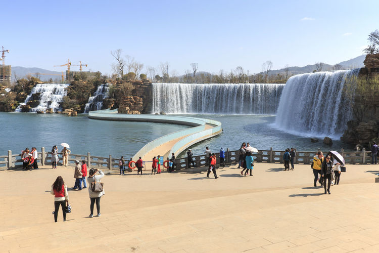 Kunming, China - March 4, 2016: Tourists wisiting the Kunming Waterfall park featuring a 400 meter wide manmade waterfall. Kunming is Yunnan's capital ASIA China Dalí Dianchi Lake Indochina IndoChinaSails Kunming, China Lijiang Niulan River Southeast Asia Waterfall Park Yunnan
