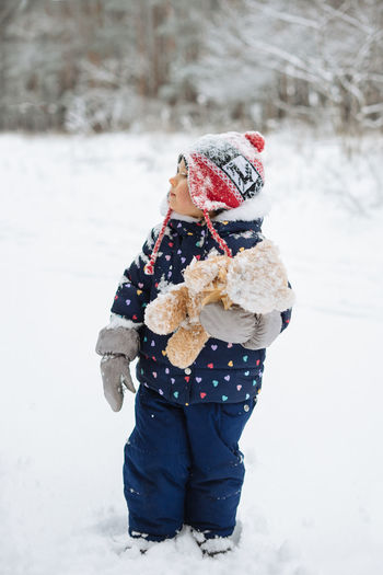 Toddler child standing outside in winter scenery holding soft toy.