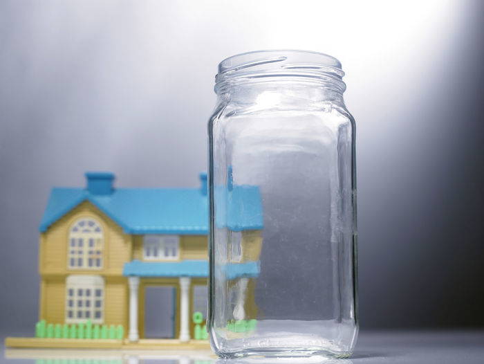 Close-up of empty jar with model home on table