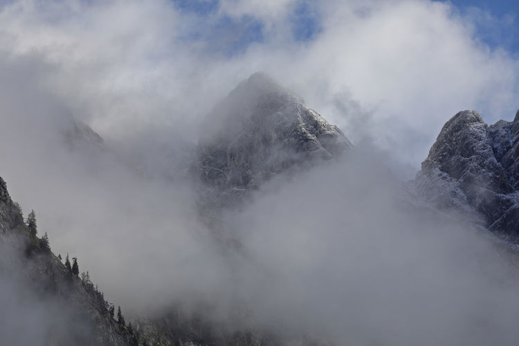 Low angle view of snow covered mountains against sky