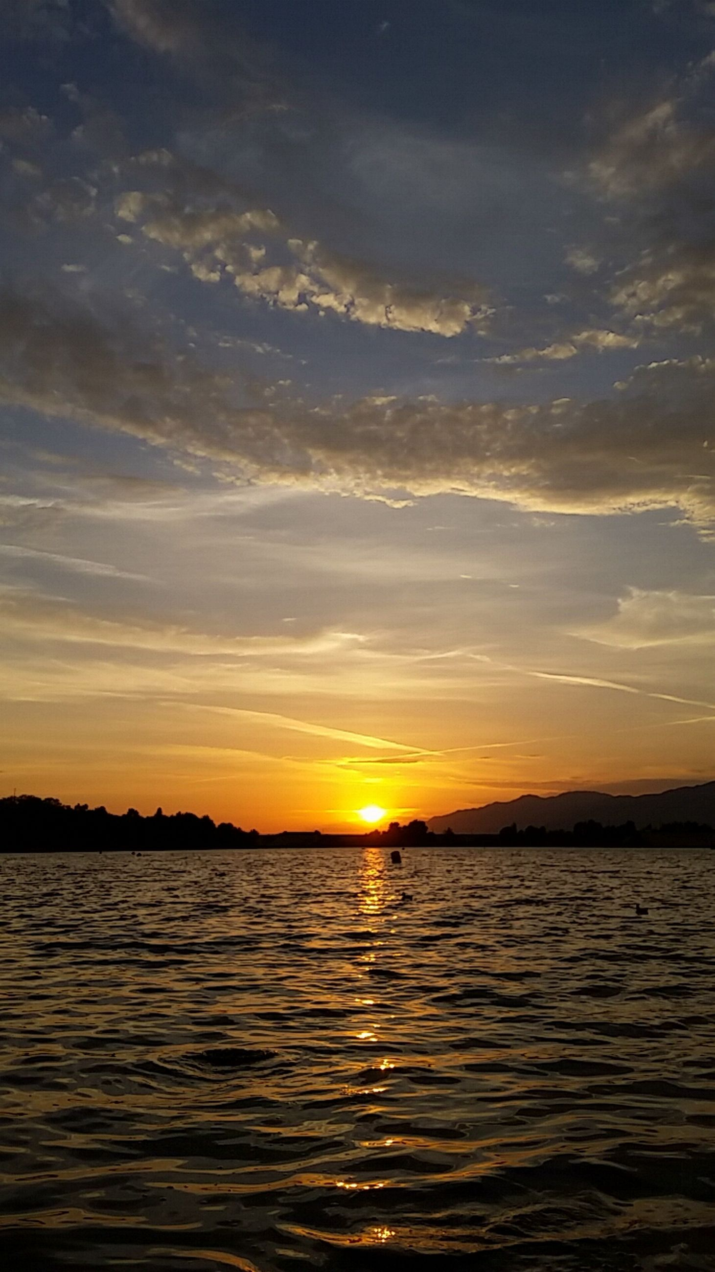 sunset, water, scenics, waterfront, tranquil scene, tranquility, sky, beauty in nature, sun, sea, orange color, rippled, nature, idyllic, reflection, silhouette, cloud - sky, sunlight, cloud, outdoors