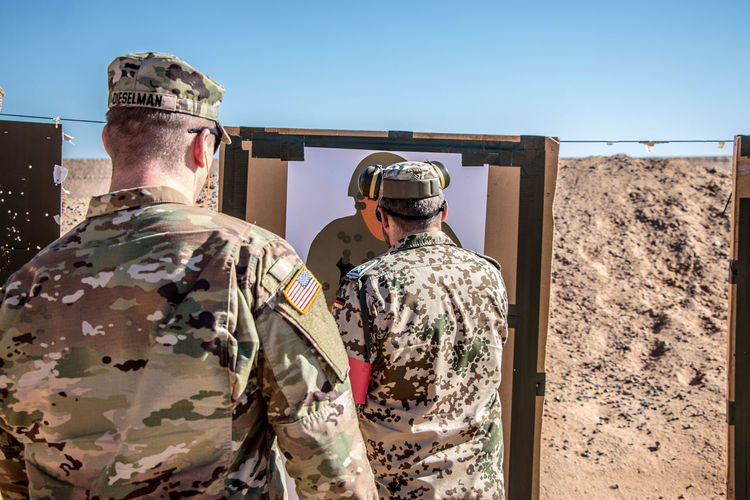 Qualifying for the German Proficiency Badge. Armed Forces Army Army Soldier Camouflage Clothing Clear Sky Clothing Day Government Men Military Military Uniform Nature Outdoors Real People Rear View Responsibility Sky Standing Sunlight Two People Uniform