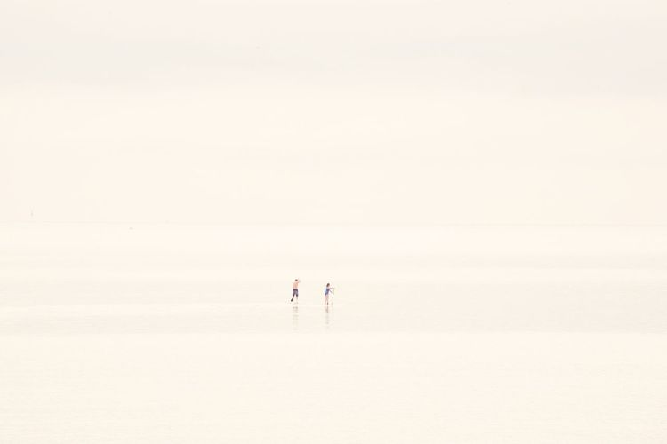 Couple Paddleboarding In Sea During Fog
