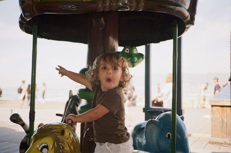 Portrait of girl in amusement park against sky
