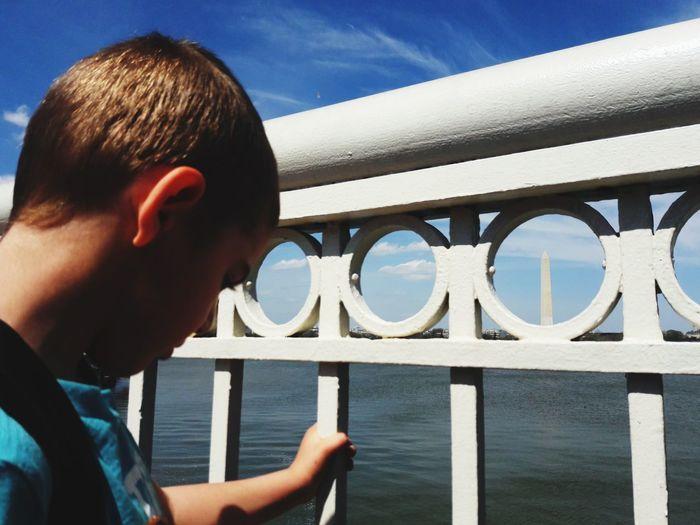 Close-up portrait of boy on railing against sky
