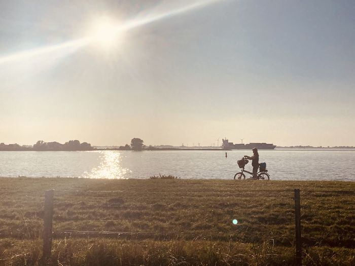 People riding bicycle on field by lake against sky