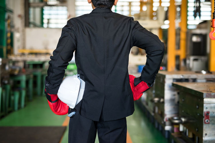 Rear view of man wearing suit and glove standing in factory