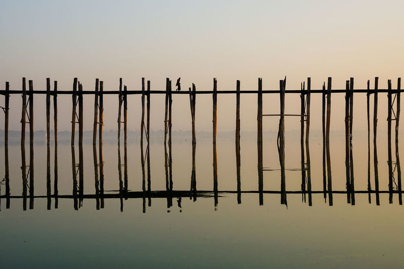 Silhouette fence by wooden post against sky during sunset