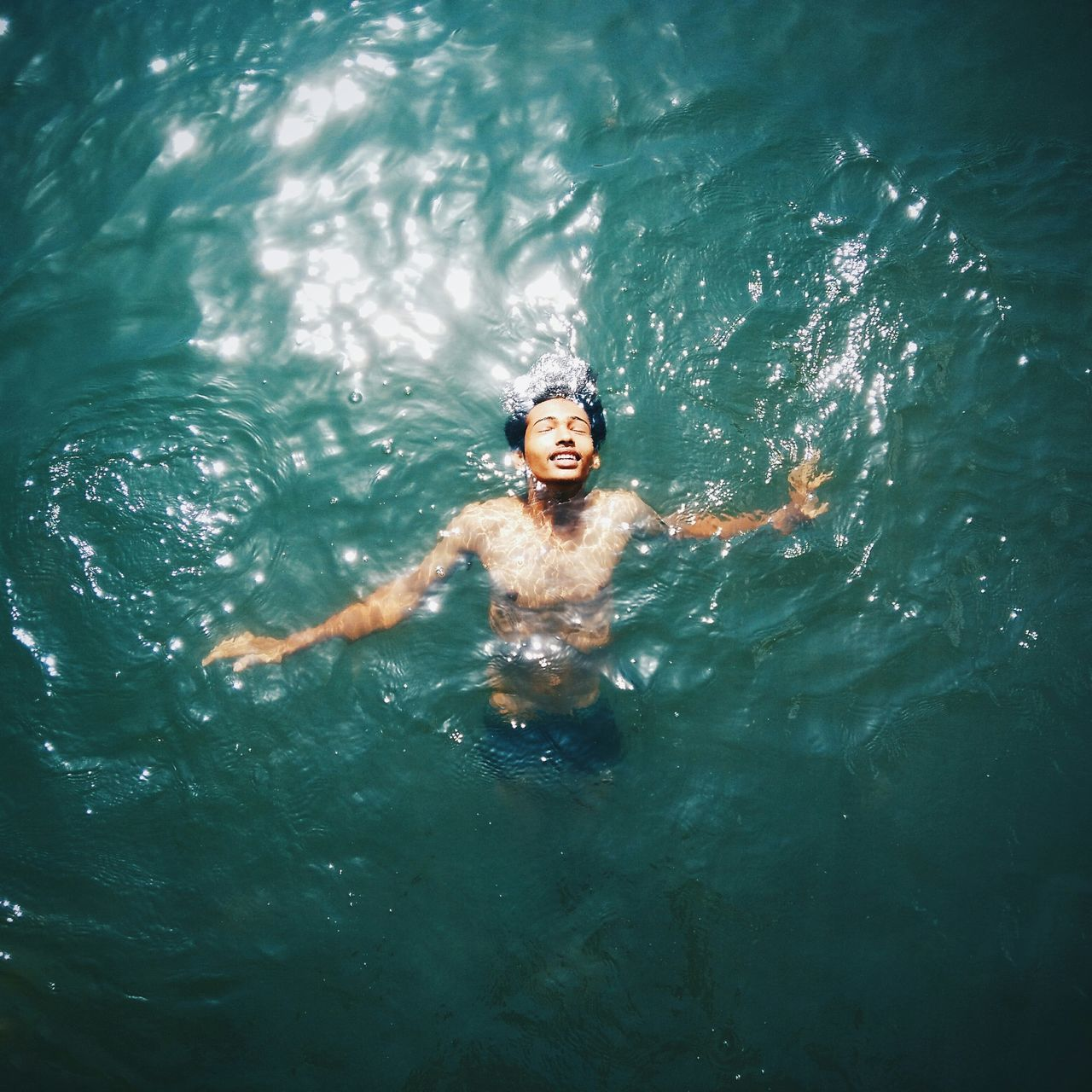 High Angle View Of Shirtless Young Man Swimming In Sea