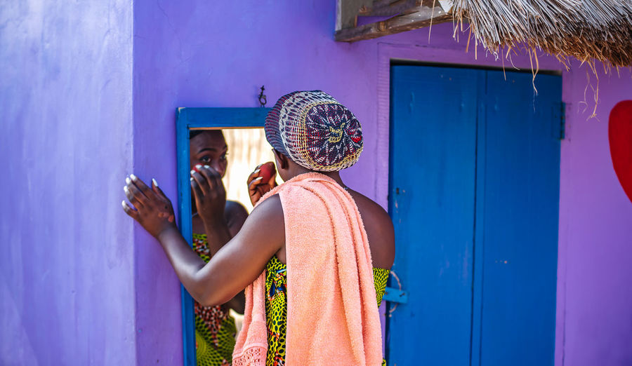 African woman doing her makeup outdoors in front of a mirror in the tropical part of ghana