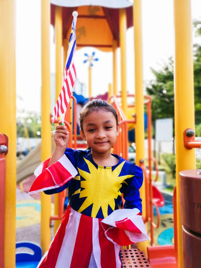 Portrait of smiling girl holding malaysian flag on jungle gym at playground
