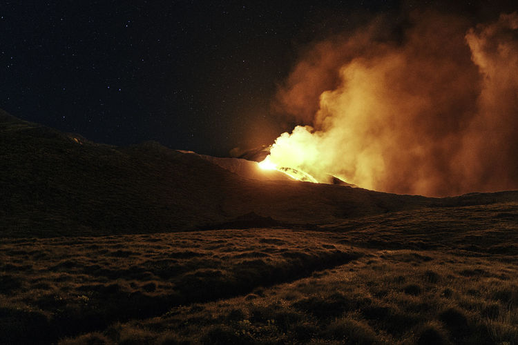 Scenic view of lava against sky at night