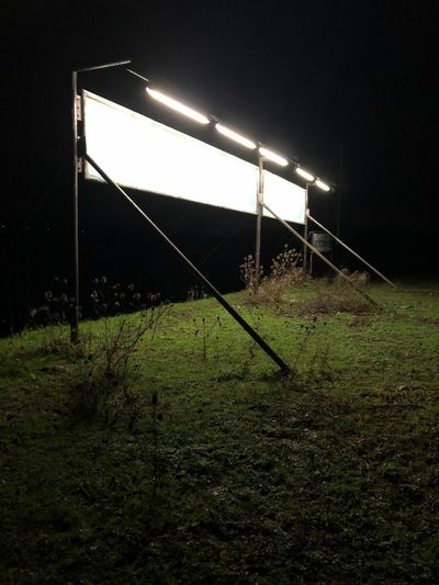 Werbe Schild in der Nacht Advertising Signs Night Grass Illuminated Land Lighting Equipment Field Plant Nature No People Built Structure Outdoors Absence Glowing