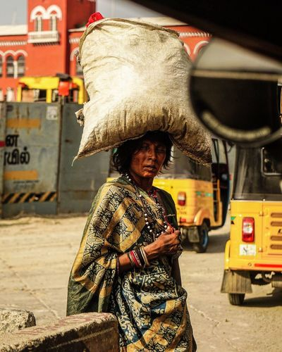Poor woman carrying sack on head in city