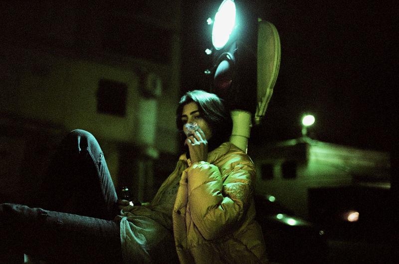 Young woman smoking cigarette at night