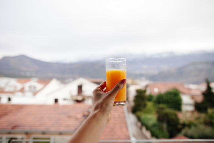 Drinking orange juice in the morning. POV EyeEm Best Shots Juice Morning POV Day Drink Drinking Glass Food And Drink Freshness Holding Human Hand Lifestyles Mountain One Person Orange Juice  Outdoors Real People Refreshment Sky