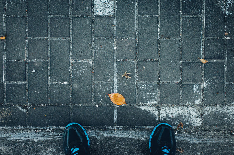 Autumn leaf on the tiled floor / looking down own foot - pov shot