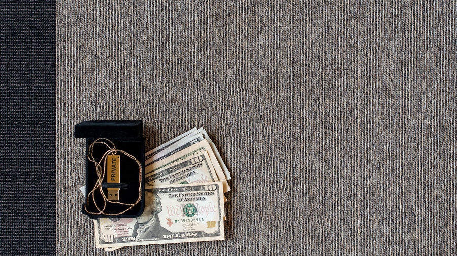 Directly above shot of hard drive and usb stick with money on carpet