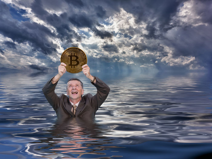 Businessman holding bitcoin in sea against stormy clouds