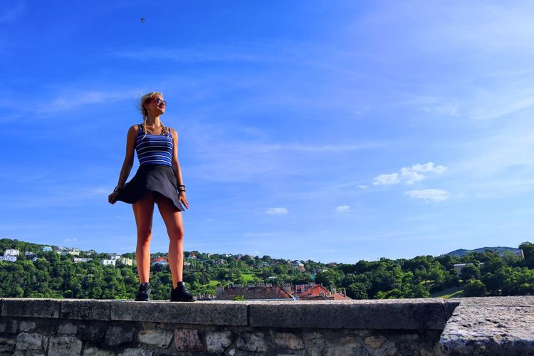 Low angle view of woman standing on retaining wall against sky