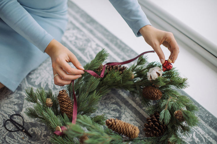 Midsection of woman decorating wreath on floor