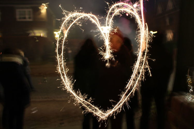 Arts Culture And Entertainment Blurred Motion Celebration Firework Firework - Man Made Object Firework Display Glowing Heart Shape Illuminated Leisure Activity Lifestyles Long Exposure Love Men Motion Night One Person Outdoors People Real People Sparkler Standing Wire Wool Women