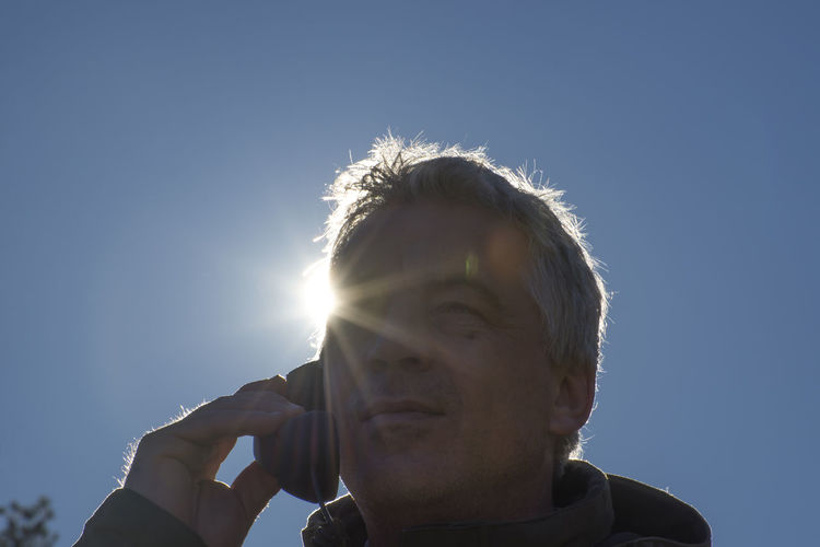Low angle portrait of man against clear sky