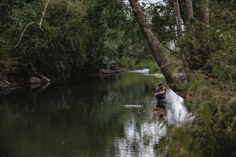 Man fishing in river at forest