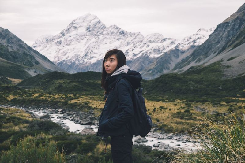 Woman standing on snowcapped mountains against sky