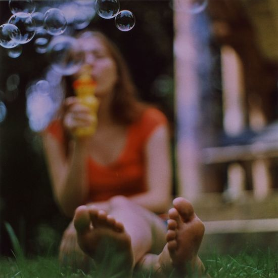 Full Length Of Young Woman Blowing Bubbles While Sitting In Back Yard
